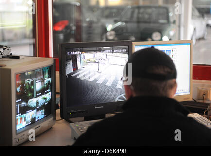 A security guard watches surveillance camera screens in  the car park where 11 year old Lena was murdered about - Stock Photo