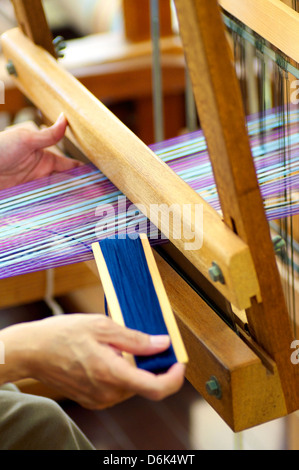 Woman working on a traditional, manual loom, weaving. - Stock Photo