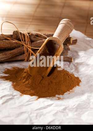 Heap of ground licorice and bundled liquorice roots - Stock Photo