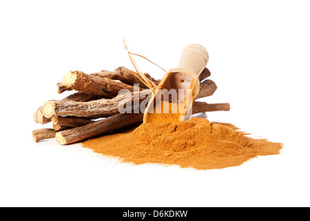 Heap of ground liquorice with wooden shovel and bundle of native liquorice roots - Stock Photo