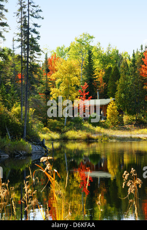 Wood cabin by a lake in beautiful fall forest - Stock Photo