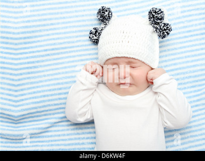 little baby crying on bed - Stock Photo