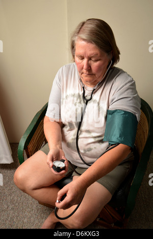 A senior female patient, who takes the prescription medication Losartan 100 mg to treat hypertension, checks her - Stock Photo