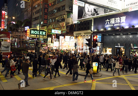 Hong Kong, China, people will cross a street at night in Kowloon district - Stock Photo