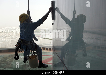 Dubai, United Arab Emirates, window cleaners at work on a glass facade - Stock Photo
