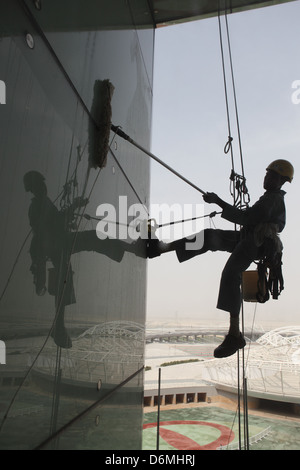 Dubai, United Arab Emirates, silhouette, window cleaners at work on a glass facade