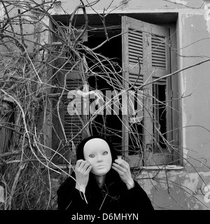 Figure with white mask under window with overgrown plants and doll hand. Black and white. - Stock Photo