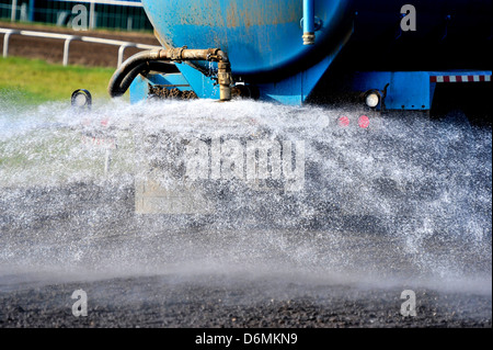 Water being sprayed on an oval race track at a rodeo event in Alberta Canada - Stock Photo