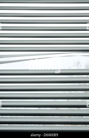 Peeking through the slats of venetian blinds. - Stock Photo