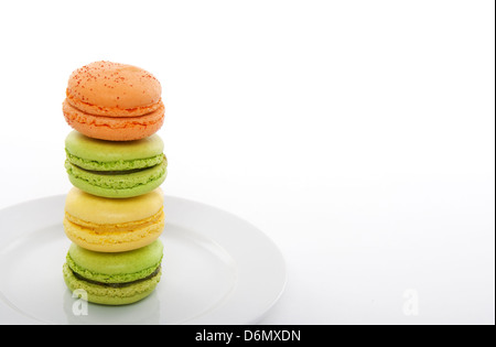 French dessert, colorful macarons on a white plate. - Stock Photo