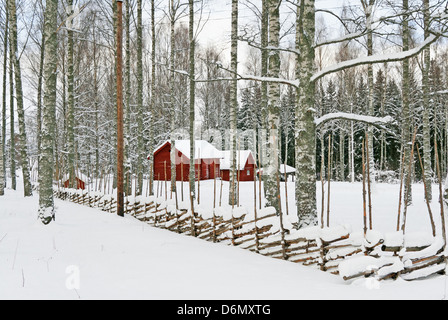 Traditional Swedish red wooden houses in a snowy landscape. - Stock Photo
