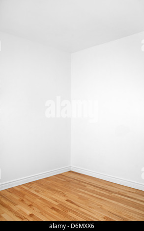 Empty corner of a renovated room with white walls and wooden floor. - Stock Photo