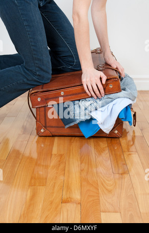 Young woman in jeans trying to close her suitcase with too much clothing. - Stock Photo