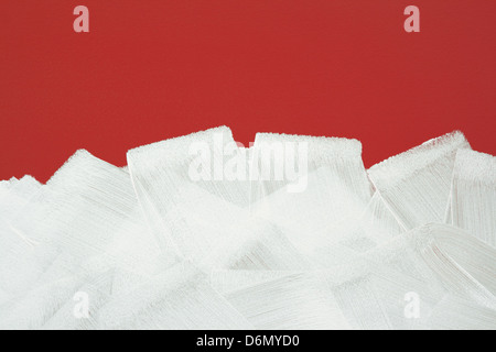 Bright red wall painted in white with paint roller. Brush strokes texture. - Stock Photo