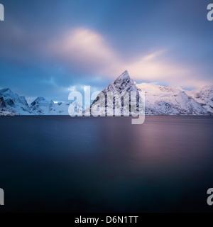 Winter sunrise on snow covered Olstind mountain peak rising from Fjord, Toppøya, Moskenesøy, Lofoten Islands, Norway - Stock Photo