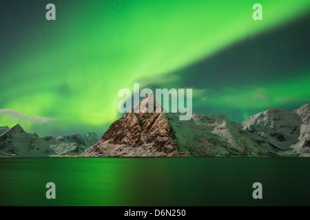 Aurora Borealis - Northern Lights fill sky over Olstind mountain peak and reflect in fjord, Toppøya, Lofoten Islands, - Stock Photo