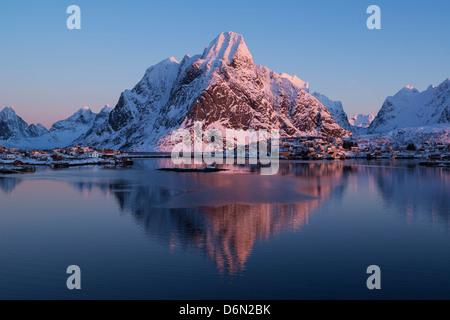 snow covered Olstind mountain peak glows pink in winter sunrise, Reine, Lofoten Islands, Norway - Stock Photo
