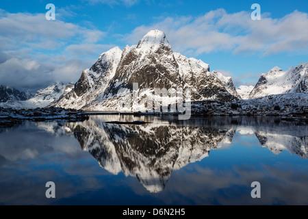 Snow covered Olstind mountain peak rising above Reine, Moskenesøy, Lofoten Islands, Norway - Stock Photo