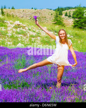 Happy blond woman with floral bouquet dancing on purple lavender field, having fun outdoors, summer vacation concept - Stock Photo