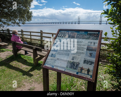 WALES COAST PATH AT BLACK ROCK WITH WALKER SITTING ON BENCH AND SECOND SEVERN CROSSING IN BACKGROUND. - Stock Photo