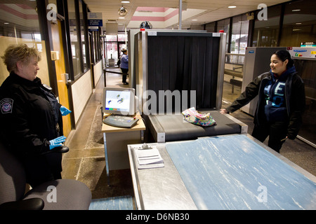 A US Customs and Border Protection officer watches the X-Ray scanner at the San Luis border pedestrian entrance - Stock Photo