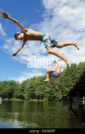 Emstal, Germany, boys jumping into the water in the pool - Stock Photo