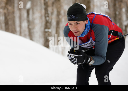 A classic style cross country skier tucks going down a hill during the American Birkebeiner in Northern Wisconsin. - Stock Photo