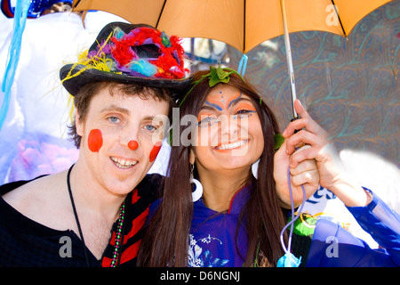 Asian woman and white man age 23 in costume having fun carrying parasol. MayDay Parade and Festival Minneapolis - Stock Photo