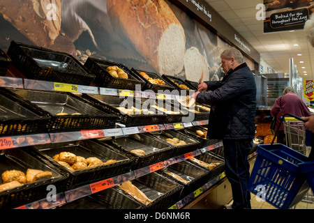 A man choosing freshly baked bread and other items from the bakery display at Lidls supermarket, Aberystwyth UK - Stock Photo