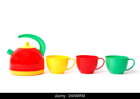teapot and three cups in row toys isolated on white - Stock Photo