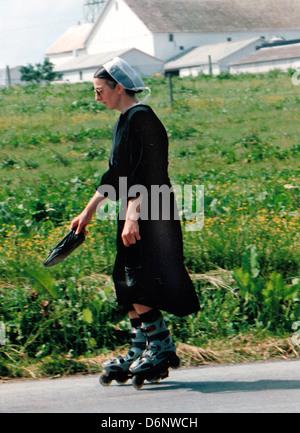 Pennsylvania Dutch girl roller blade back roads in farm land, Amish, Pennsylvania Dutch, Amish, Amish Mennonites, - Stock Photo