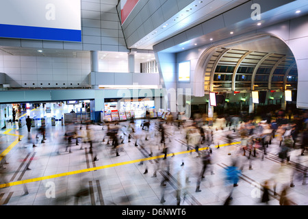 Crowds pass through a busy train station in Shinagawa, Tokyo, Japan - Stock Photo