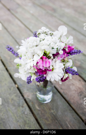 Pink , white and purple bouquet of flowers informally arranged in a glass jar on wooden decking - Stock Photo