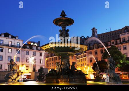 Illuminated fountain at night, Rossio Square (Praca do Dom Pedro IV), in the Baixa district of Lisbon, Portugal, - Stock Photo