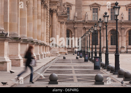 A woman walks through the Louvre Museum in Paris, France, Europe - Stock Photo