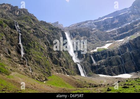 Waterfalls cascade down the karst limestone cliffs of the Cirque de Gavarnie, Pyrenees National Park, Hautes-Pyrenees, - Stock Photo