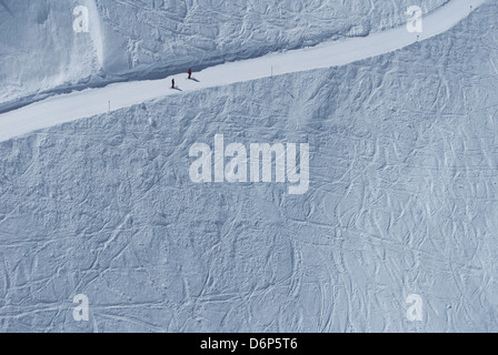 View of two skiers on a piste, from a cable car, above St Anton in the Austrian Tyrol - Stock Photo