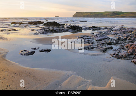 Tide retreating at sunset leaving tide pools among rocks, with Pentire Head in the background, Polzeath, Cornwall, - Stock Photo