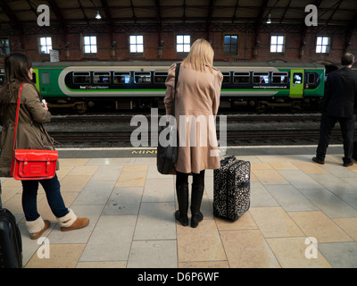 People with luggage waiting for a train on the platform at Bristol Temple Meads railway station Bristol England - Stock Photo