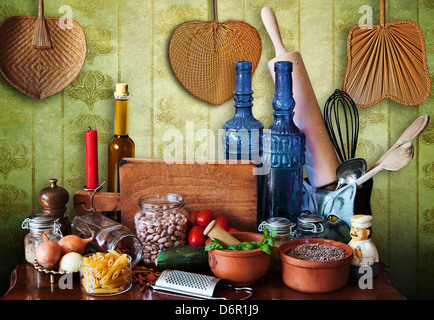 Kitchen still life in Mediterranean style, rolling pin, glass bottles, vegetables, noodles,onions, legumes,tomatoes - Stock Photo