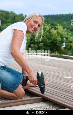 Young woman with screwdriver attaching wooden planks on a terrace - Stock Photo