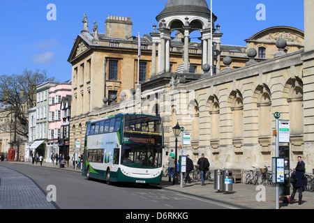 Electric Hybrid double deck bus in High Street, Oxford outside The Queen's College, part of Oxford University. - Stock Photo
