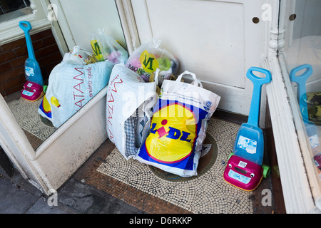 Bags of donated goods left outside a branch of Oxfam charity shop, UK - Stock Photo