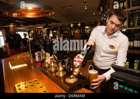 A barman pulling a pint of draught beer real ale, in a pub UK - Stock Photo