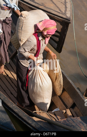 Woman carrying sacks off a boat, Inle Lake, near Indein and Nyaung Ohak villages, Shan State, Myanmar, (Burma) - Stock Photo