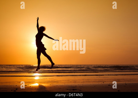 silhouette of happy woman jumping on the beach, healthy lifestyle - Stock Photo