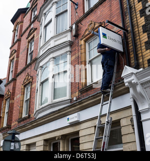 Working at height: A workman standing on a ladder replacing repairing the sign outside a branch of Lloyds TSB bank, - Stock Photo