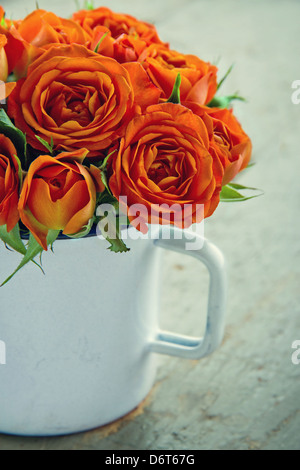 White mug with a bouquet of orange roses on green vintage wooden background - Stock Photo