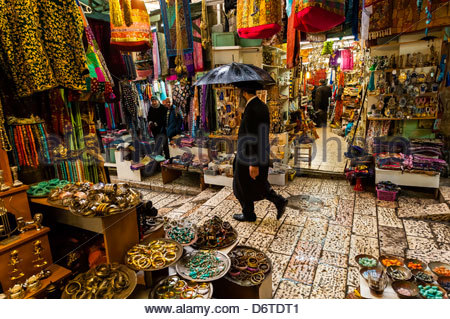 An orthodox Jew walking through the Arab bazaar (suq) in the old city of Jerusalem, Israel in the rain. - Stock Photo