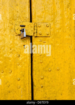Padlock on an old yellow metallic door - Stock Photo